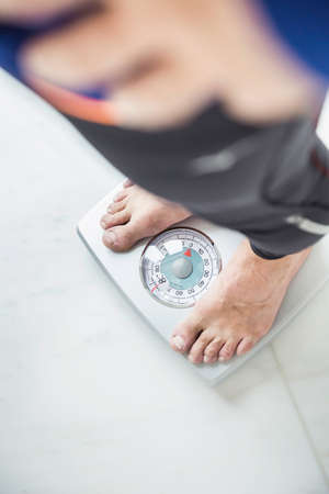 Overhead view of mature man weighing himself on bathroom scales