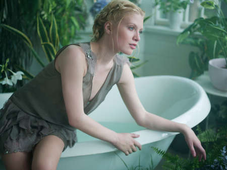 Young woman sitting on edge of bathtub, in bathroom filled with plants LANG_EVOIMAGES