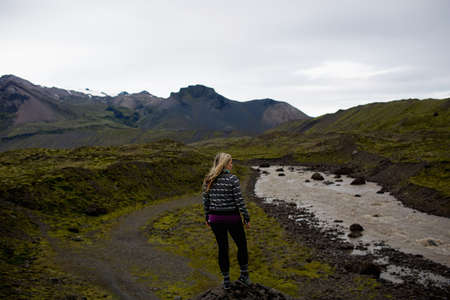 Rear view of mid adult woman by river looking at mountain range, Iceland LANG_EVOIMAGES