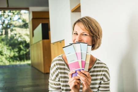 Portrait of mature woman holding swatches in new house