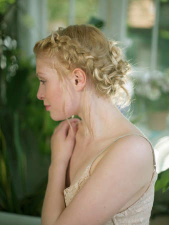 Young woman, with blonde plaited hair, looking away, close-up