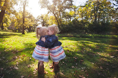 in unison: Twin girls wearing matching dresses face to face hugging and kissing