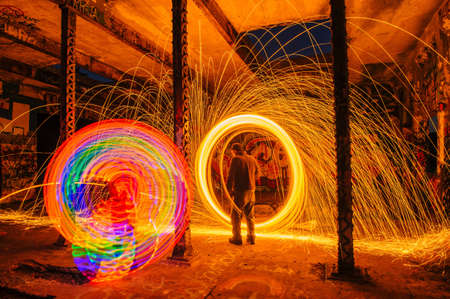 Man creating multi-color and golden spark light trails in derelict building LANG_EVOIMAGES