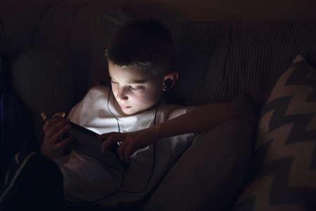 world at your fingertips: Boy on sofa wearing earphones looking down using digital tablet