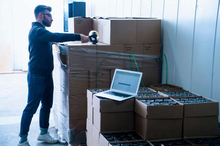 sealing tape: Side view of young man in warehouse sealing up cardboard boxes of beer with sticking tape LANG_EVOIMAGES