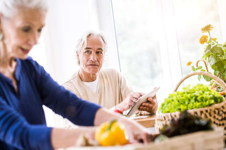 Senior couple using digital tablet and preparing food at kitchen counter