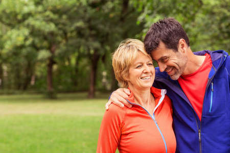 54: Couple wearing sports clothing, outdoors, hugging, smiling LANG_EVOIMAGES