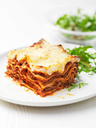 Plate of beef lasagna with salad leaves LANG_EVOIMAGES