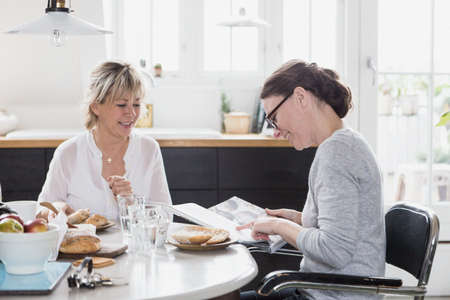 Two mature women sitting at kitchen table, having breakfast, looking through book