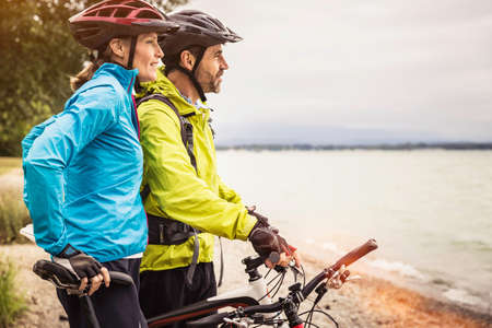 Mature mountain biking couple looking out from lakeside LANG_EVOIMAGES
