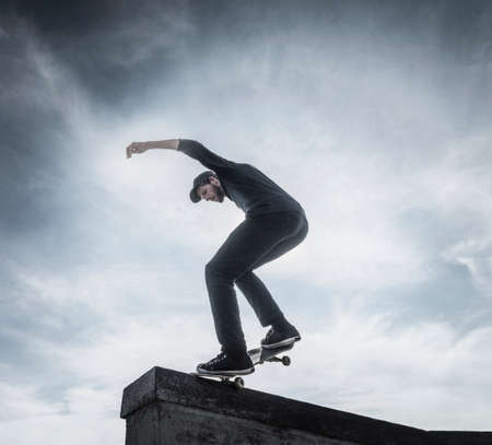 Young man skateboarding on roof LANG_EVOIMAGES