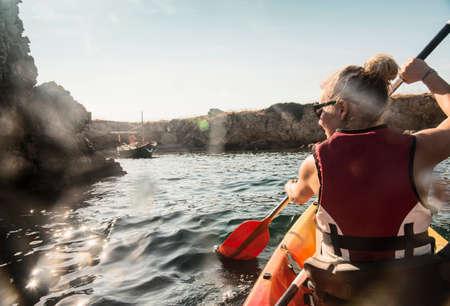 Rear view of woman sea kayaking, Menorca, Balearic islands, Spain