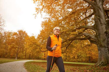 Senior female nordic walker striding in autumn park LANG_EVOIMAGES