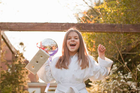 Portrait of girl celebrating trophy in garden LANG_EVOIMAGES