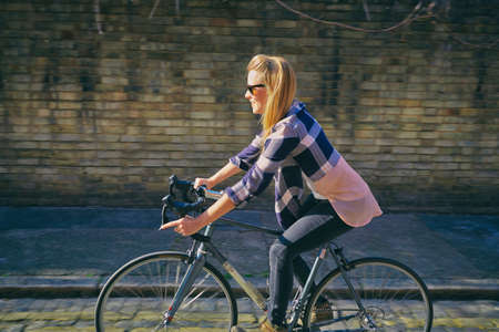 english ethnicity: Side view of mid adult woman cycling on bicycle