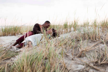 30 years old man: Couple lying in sand dunes, face to face