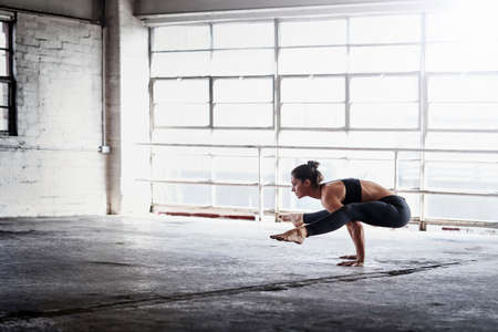 Woman practicing yoga in front of warehouse window