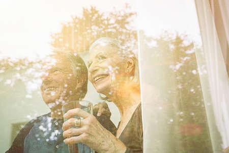 View through window of senior couple holding tumbler looking away smiling LANG_EVOIMAGES