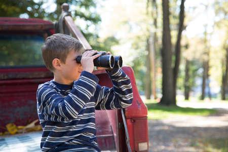 sit down: Muchacho que se inclina contra la camioneta que mira a través de los prismáticos en maderas