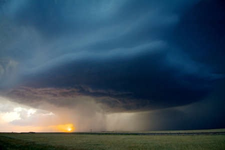 A rotating supercell storm drops hail as the sun sets behind it, Near Stratton, Colorado, USA LANG_EVOIMAGES