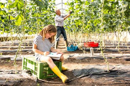 relaciones laborales: Muchacha que se sienta en el cajón en el dibujo del invernadero mientras que el abuelo trabaja detrás