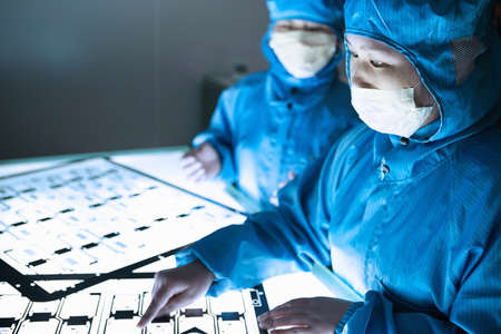 Female workers pointing at flex circuit on lightbox in flexible electronics factory clean room
