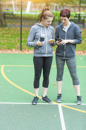 Full length front view young women standing on sports court looking down at smartphones