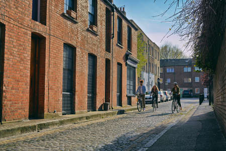 english ethnicity: Angled view of women cycling on bicycles past warehouse on cobblestone road LANG_EVOIMAGES