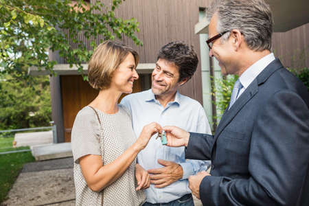 sold small: Estate agent handing keys to mature couple at new house LANG_EVOIMAGES