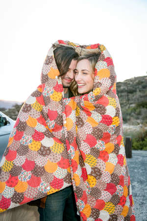 groovy: Young couple wrapped in patchwork blanket smiling LANG_EVOIMAGES
