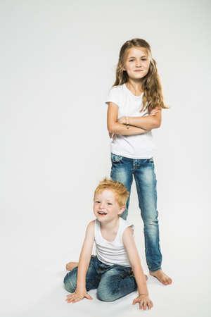 Studio portrait of boy and sister LANG_EVOIMAGES