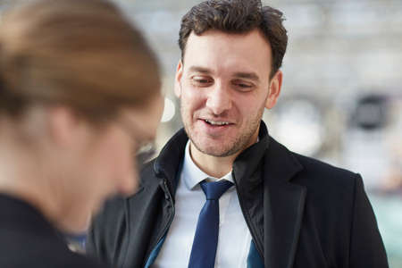 Business man talking to colleague looking down smiling