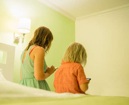 Mother and son using smartphone on bed