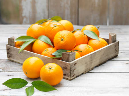 Oranges in vintage crate on whitewashed wooden table