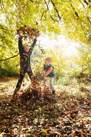 curiousness: Children playing, arms raised, throwing autumn leaves LANG_EVOIMAGES