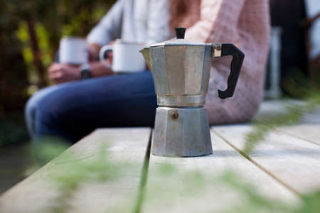 Cropped shot of couple sitting on garden porch with coffee pot