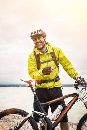 Portrait of mature male mountain biker at lakeside LANG_EVOIMAGES