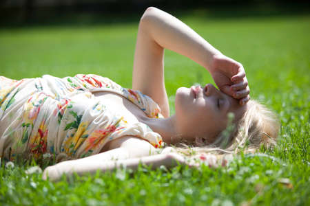Young woman lying on grass, eyes closed