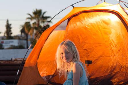 Vista lateral de la niña junto a la tienda de color naranja, mirando a la cámara sonriendo