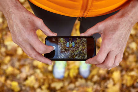 body parts cell phone: Cropped shot of senior woman photographing autumn park leaves on smartphone