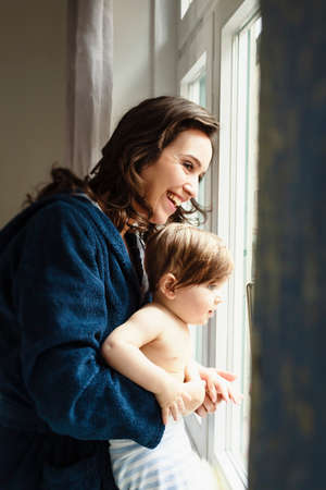 niños vistiendose: Madre y bebé hijo mirando por la ventana