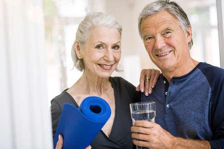 Senior man and woman holding yoga mat and tumbler of water looking at camera smiling LANG_EVOIMAGES