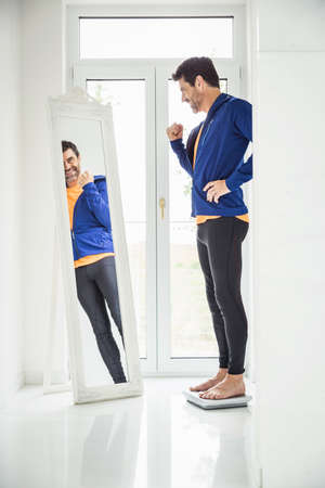 Happy mature man weighing himself whilst looking in mirror at home LANG_EVOIMAGES