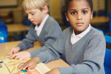 Portrait of boy doing puzzle at desk in elementary school classroom