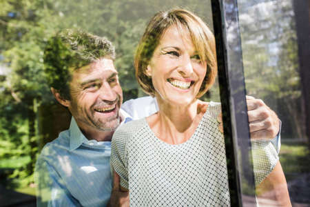 54: Happy mature couple looking through window of new house LANG_EVOIMAGES