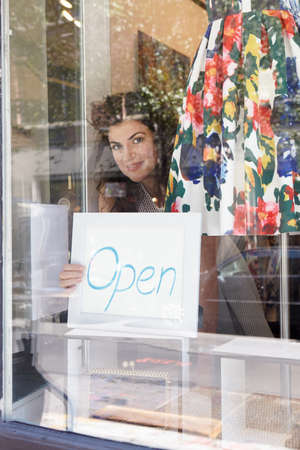 salespeople: Female business owner placing open sign in window of fashion boutique