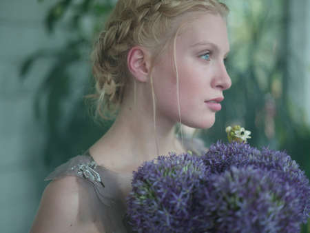 purples: Young woman, holding bouquet of flowers, close-up LANG_EVOIMAGES