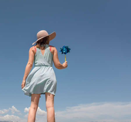 obscuring: Rear view of woman with hat holding paper windmill