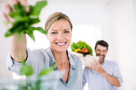 54: Mature woman with handful of salad leaves in kitchen