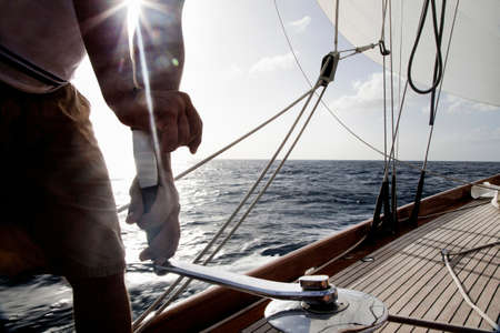 turn away: Man turning winch handle on classic sail yacht